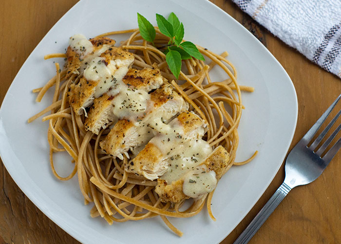 White Cheddar Chicken Pasta garnished with a sprig of basil on a square white plate next to a stainless steel fork with a white and brown towel behind all on a wooden surface