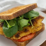 Fried tilapia sandwich wiht sliced tomato and fresh spinach on a square white plate with a white towel behind on a wooden surface (vertical with title overlay)