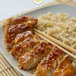 Orange chicken on a white plate with brown rice and chopsticks (with title overlay)