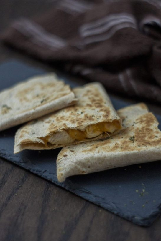 3 pieces of chicken and cheese quesadillas on a slate tray with a brown and white towel behind all on a wooden surface (vertical)