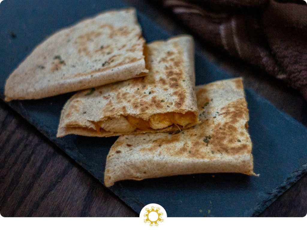 3 pieces of chicken and cheese quesadillas on a slate tray with a brown and white towel behind all on a wooden surface (with logo overlay)