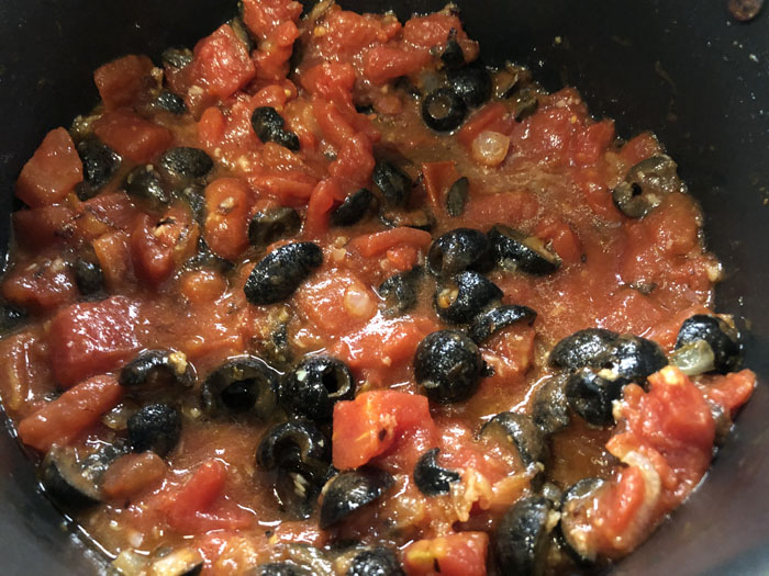 Large stockpot cooking tomatoes and black olives