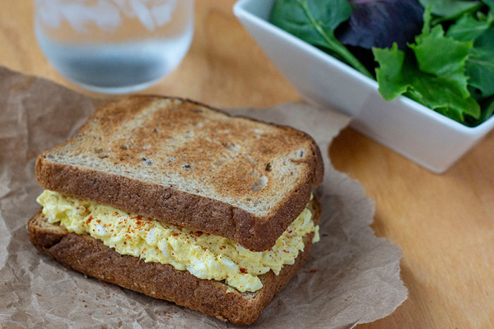 Egg Salad Sandwich on a brown piece of paper with a glass of water and white bowl of salad on a wooden surface