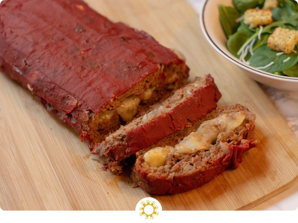 Mozzarella-Stuffed Meatloaf with a few slices laying on their side next to a bowl of salad on a bamboo surface (with logo overlay)