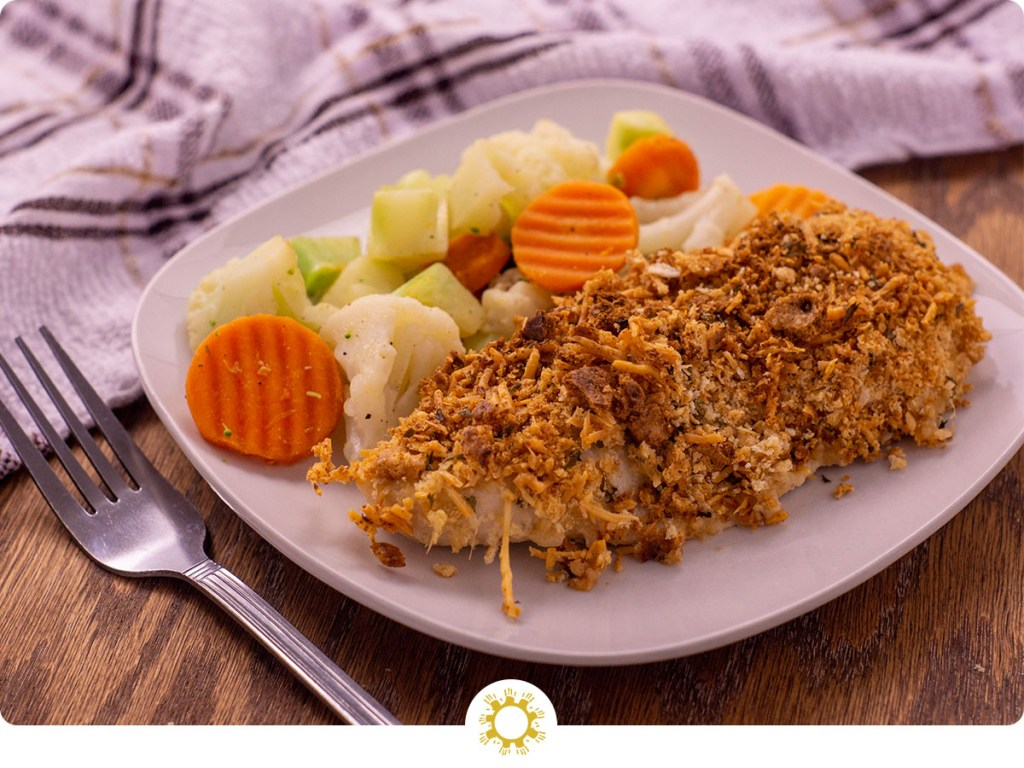 Parmesan crusted chicken next to steamed mixed vegetables on a white square plate with a white and brown towel behind all on a wooden surface (with logo overlay)