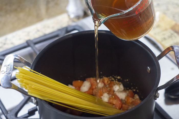 Chopped vegetables and linguine noodles in a large stockpot with broth being poured from a glass measuring cup into the pot