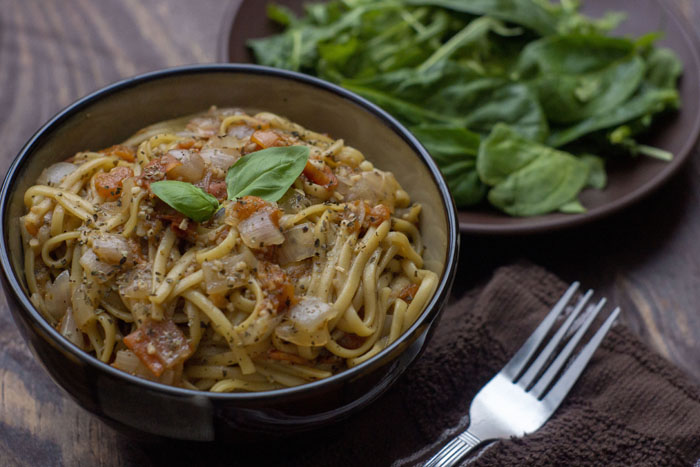 Pasta All-In in a round brown bowl topped with fresh basil leaves next to a plate of greens all on a wooden surface