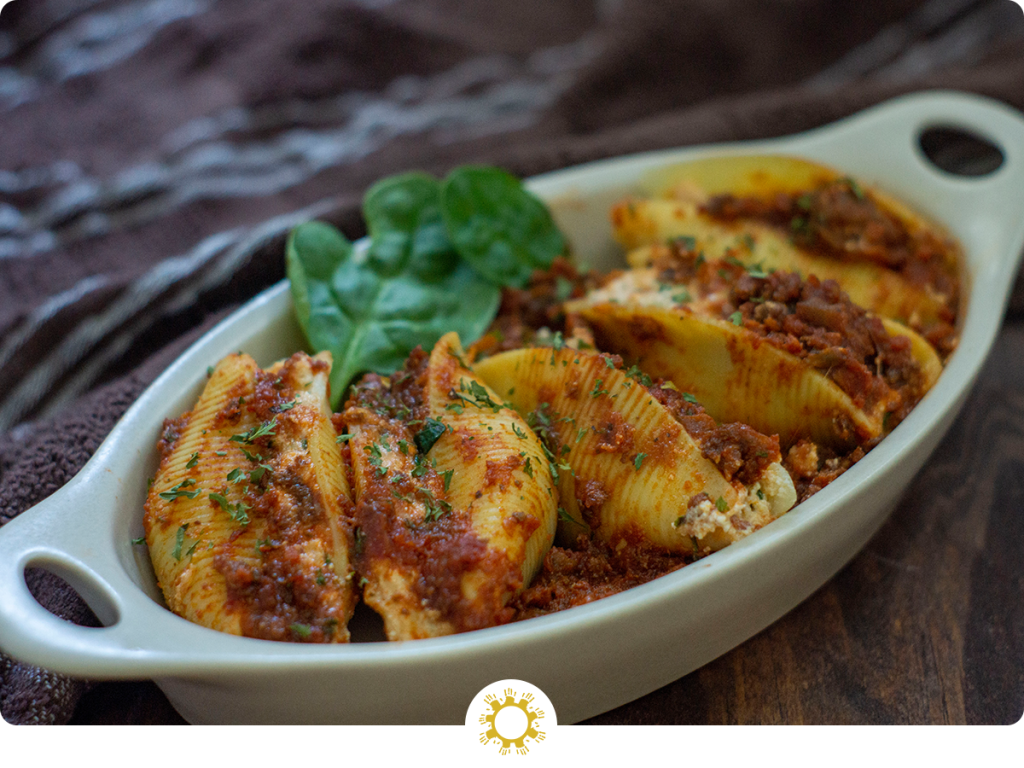 Cooked stuffed shells garnished with spinach in a white dish on a wooden surface (with logo overlay)
