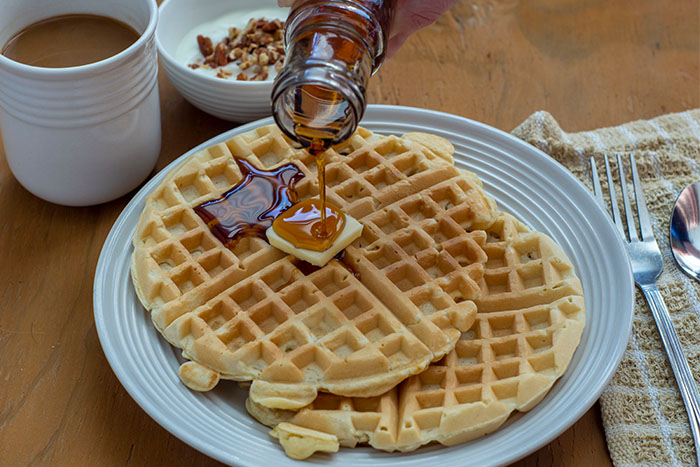 Two waffles with a pat of butter on a white plate with syrup pouring onto them next to a tan napkin with a fork and a cup of coffee and a yogurt parfait in the background on a wooden surface
