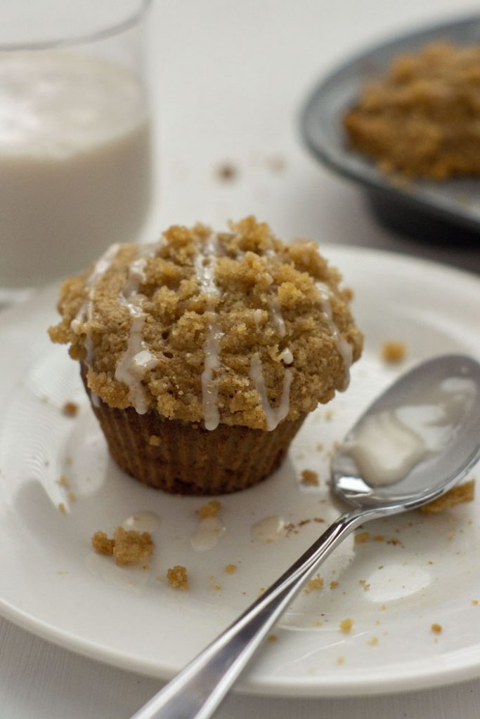 Banana Muffin drizzled with icing next to a spoon of icing and streusel crumbles on a round white plate with a glass of milk and the muffin pan behind all on a white surface (vertical)