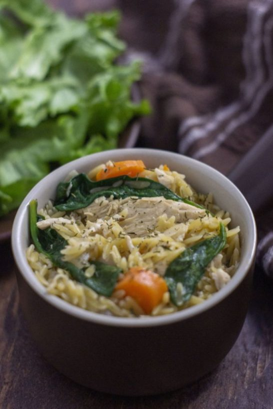 Chicken Orzo Pasta in a brown bowl next to a plate with spinach leaves and a brown towel on a wooden surface (vertical)