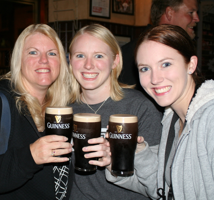 Three women in a pub in Dublin holding glasses of Guinness beer
