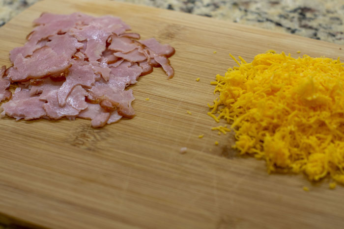 Pieces of torn ham next to shredded cheddar cheese on a bamboo cutting board on a granite countertop