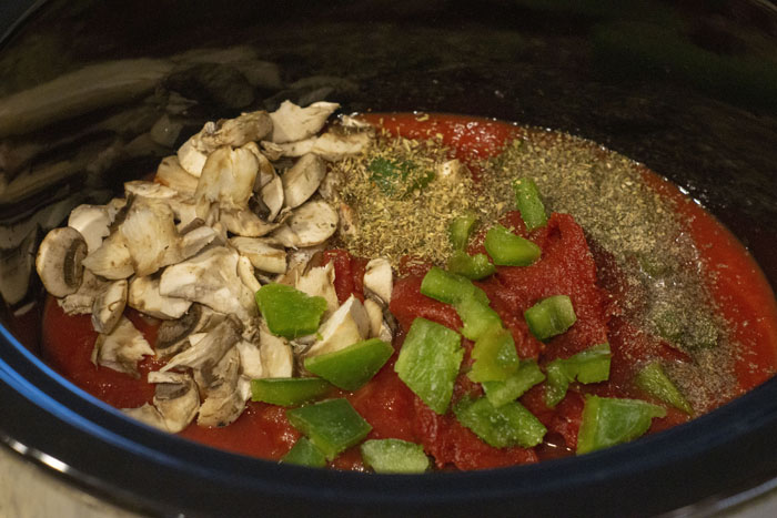 Tomat sauce, seasonings, green pepper, and mushrooms in a slow cooker