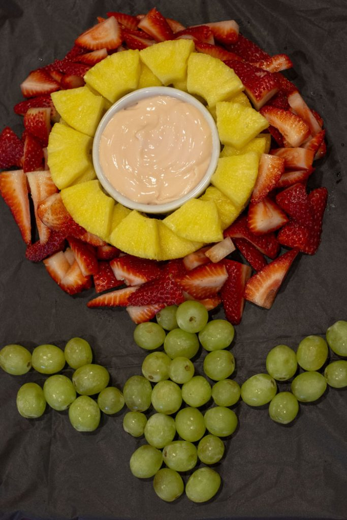 Fire flower fruit with a fruit dip in a white boel surrounded by slices of watermelon with sliced strawberries around the pineapple and grapes for the stem and leaves on a black tablecloth