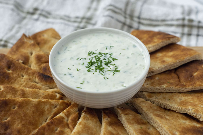 Tzatziki Sauce from Scratch garnished with dill in a large white bowl surrounded by slices of pita bread
