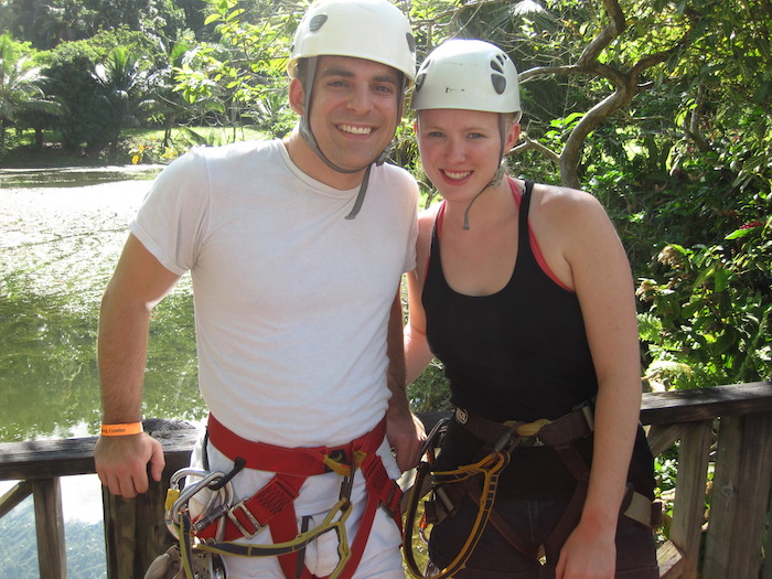 Man and Woman with helmets and harnesses on in front of a river surrounded by lush green trees