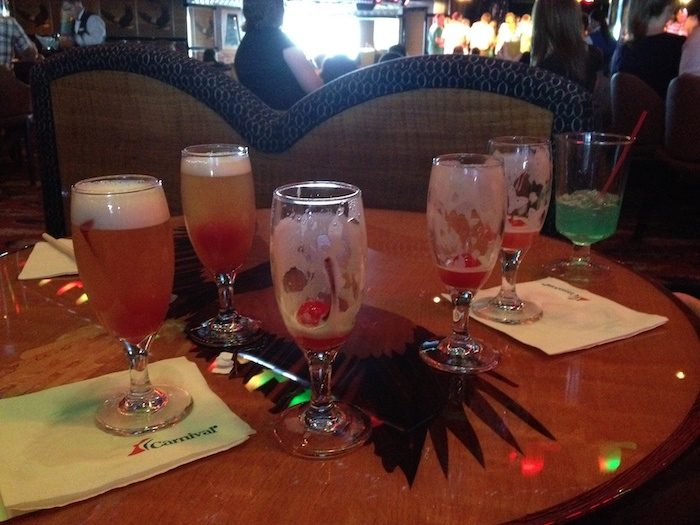 Red table covered with multiple glasses of Whiskey Sour, some full, some empty