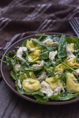 Chicken Tortellini Salad with Lemon Dressing on a round brown plate next to a brown towel on a wooden surface (vertical)