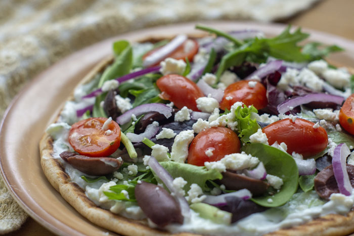 Open-Faced Greek Pita topped with sliced red onion, spinach, tzatziki sauce, sliced tomatoes, feta cheese, and greek olives on a tan plate next to a brown towel