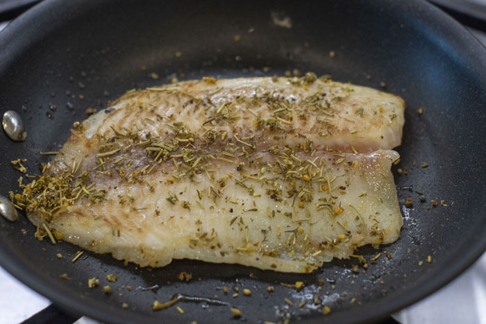 Close up of tilapia fillet in a skillet with seasonings on top
