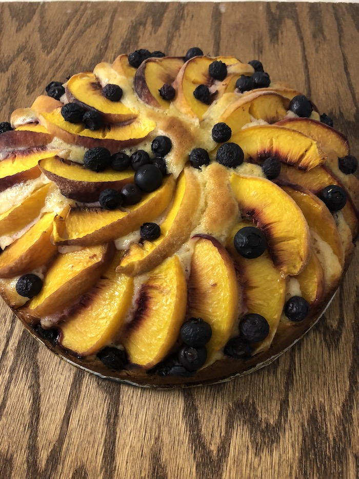 Peach and Blueberry Cake on a wooden surface (vertical)