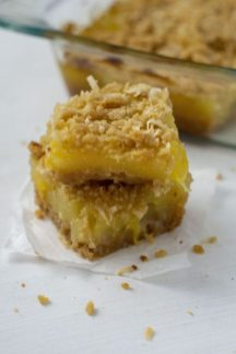 Two Pineapple Coconut Dessert Bars on a piece of parchment paper on a white surface with the glass dish of bars in the background (vertical)