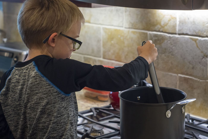 Young boy mixing ingredients in a large stock pot