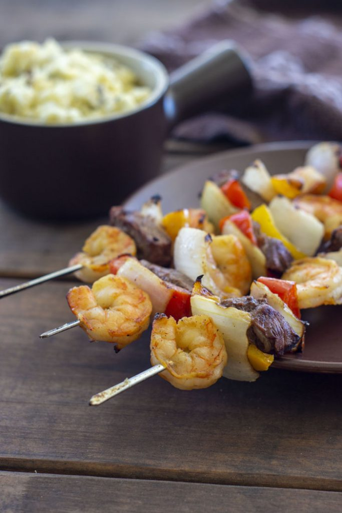 Steak and Shrimp Kabobs on a brown plate with a bowl of potato salad in the background (vertical)