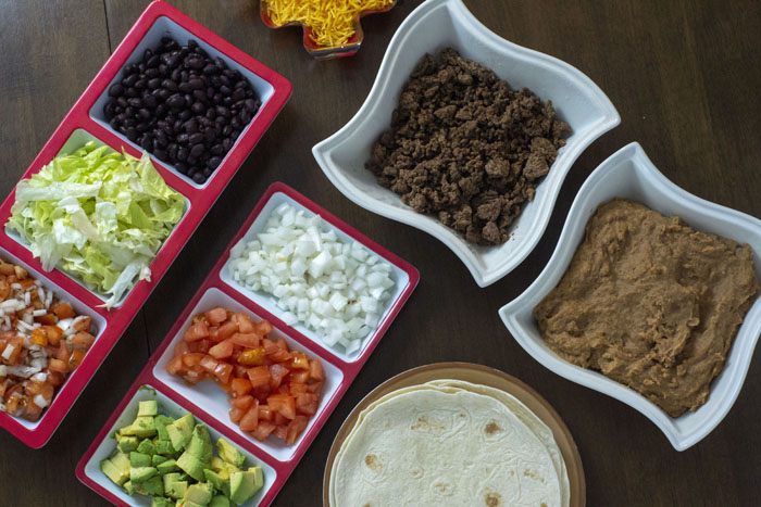 Top-down view of taco bar with each ingredient and topping in separate bowls