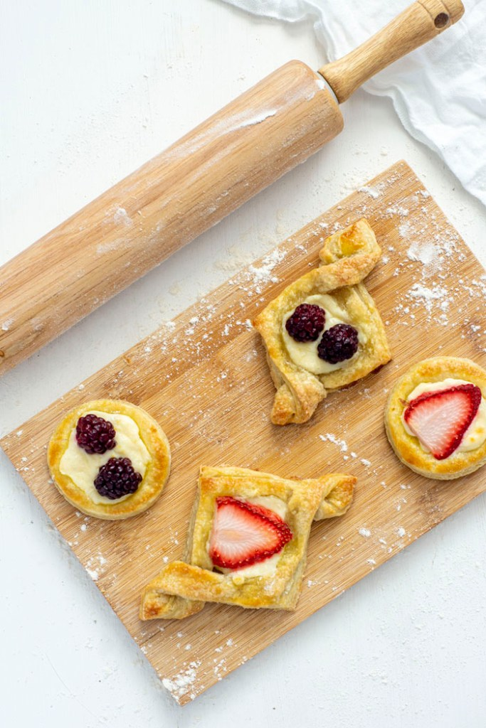 Breakfast pastries on a wooden cutting board next to a wooden rolling pin on a white background (vertical)