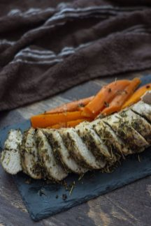 Sliced Italian-Herb Crusted Pork Tenderloin on a slate board with carrots all on a wooden background (vertical)