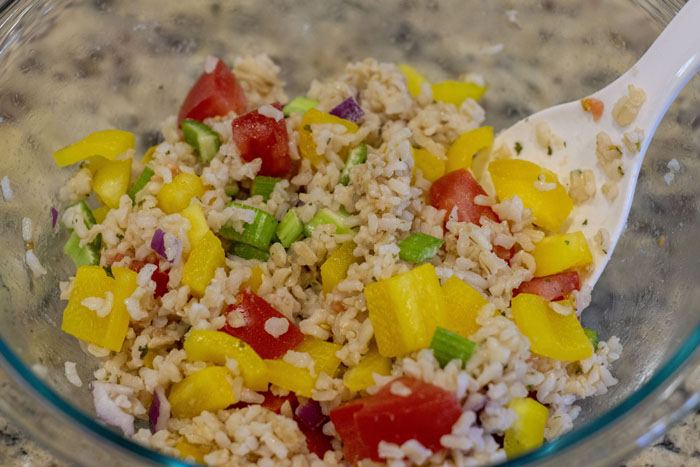 Glass mixing bowl with rice, peppers, red onion, tomato, and celery being mixed with a white paddle