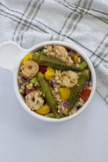 Shrimp and okra bowl recipe in a white bowl with a towel next to it (vertical)