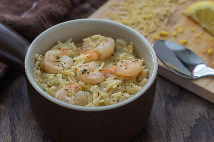 Shrimp Orzo with Lemon in a brown and white dish with a wooden board covered with orzo noodles and lemon zest next to a spoon all on a wooden surface