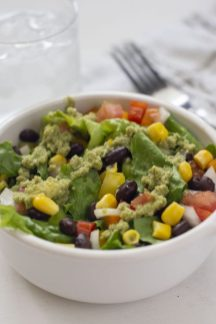 Southwestern salad with an avocado dressing in a white round bowl with a stainless steel fork and glass of water behind (vertical)
