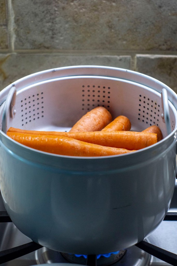 Carrots in a steamer basket over a gas stovetop