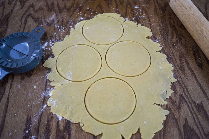Dough rolled out on a wooden surface with circles cut out