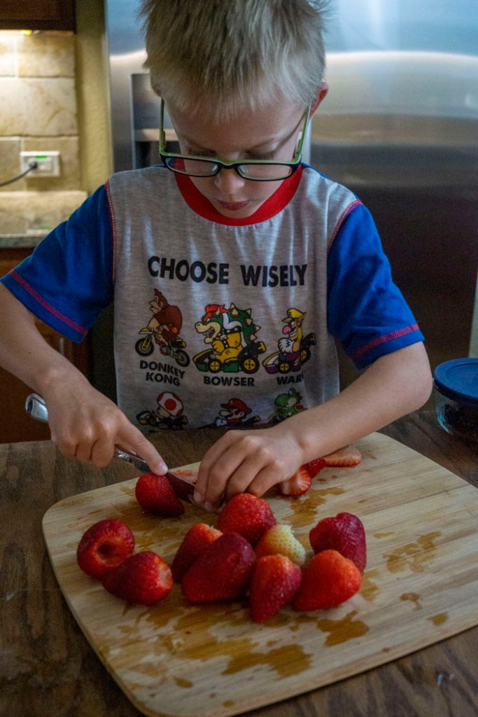 Young boy cutting strawberries on a wooden cutting board