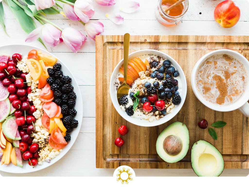 Arrangement of healthy food on white plate and bowl with a wooden cutting board