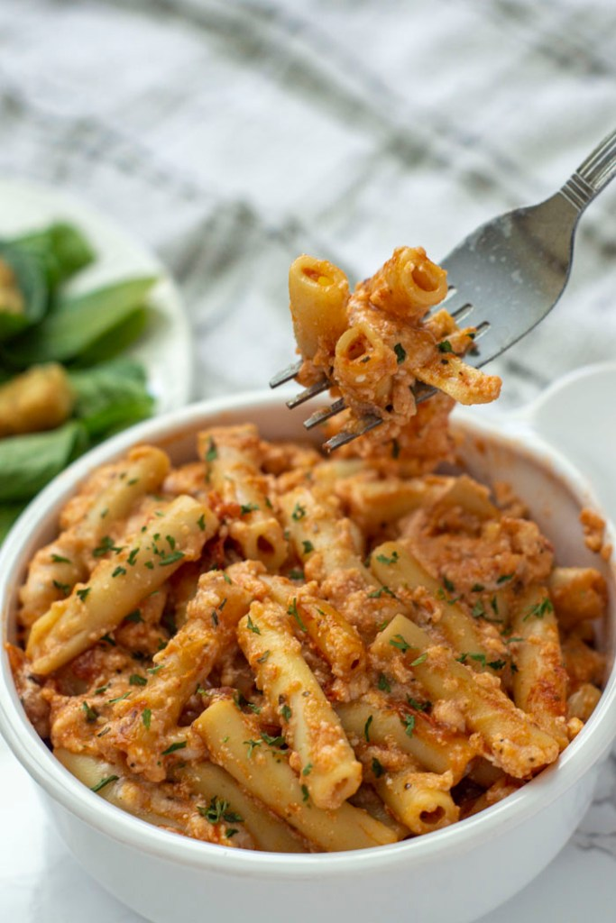 A bite of Baked Ziti in a white bowl being lifted by a fork (vertical)