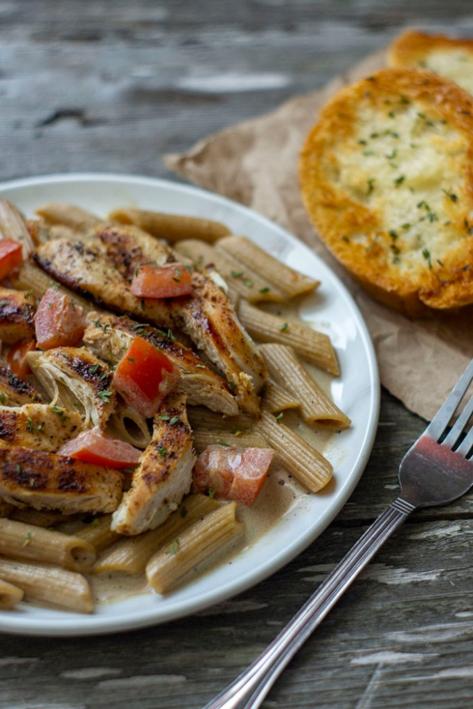 Cajun Chicken Pasta on a white plate with a fork to the right side and garlic toast in the background on a wooden surface (vertical)
