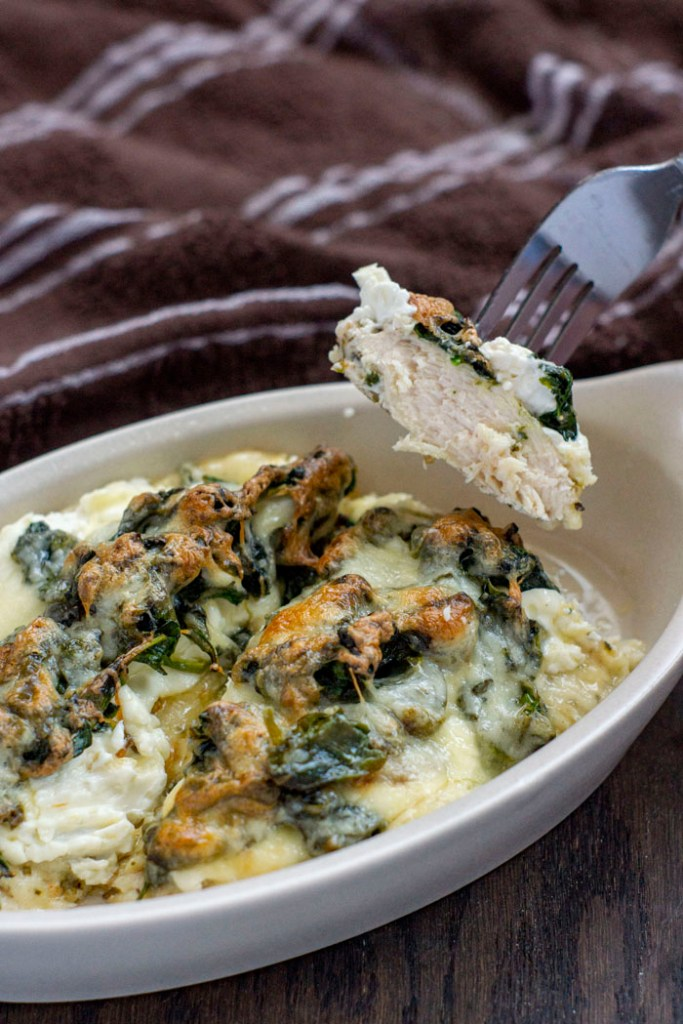 Chicken and Spinach Casserole with Cream Cheese in a tan bowl on a wooden surface with a piece of chicken held up on a fork (vertical)