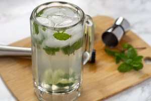 Classic Mojito in a beer mug on a wooden board with a muddler, measuring cup, and mint leaf