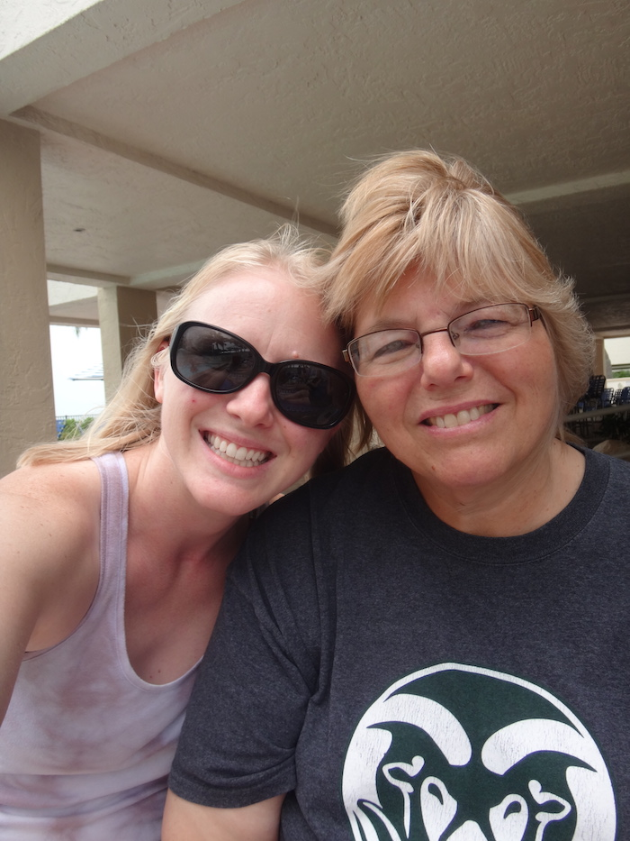 Selfie photo of two women sitting by the pool at a beach condo