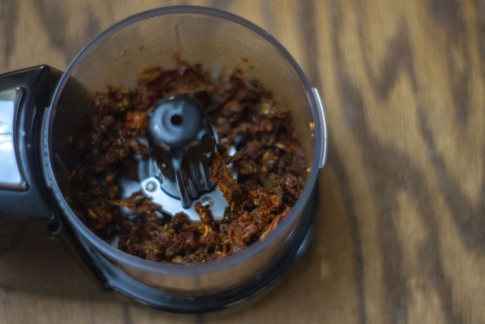 Sun-dried tomatoes in a food processor with a wooden background