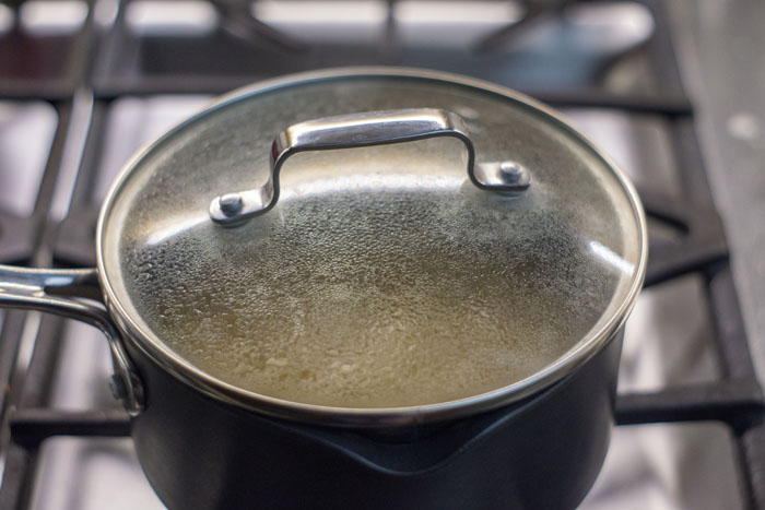 Sauce pot with lid closed over gas stovetop