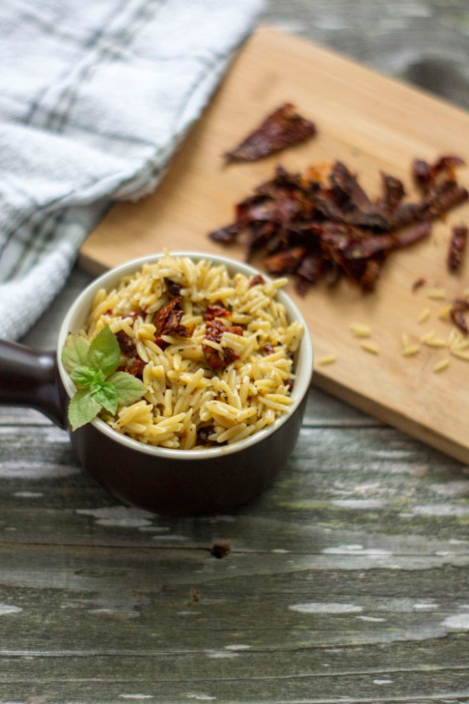 Sun-Dried Tomatoes with Basil in Orzo Pasta in a small brown dish with extra ingredients in the background (vertical)