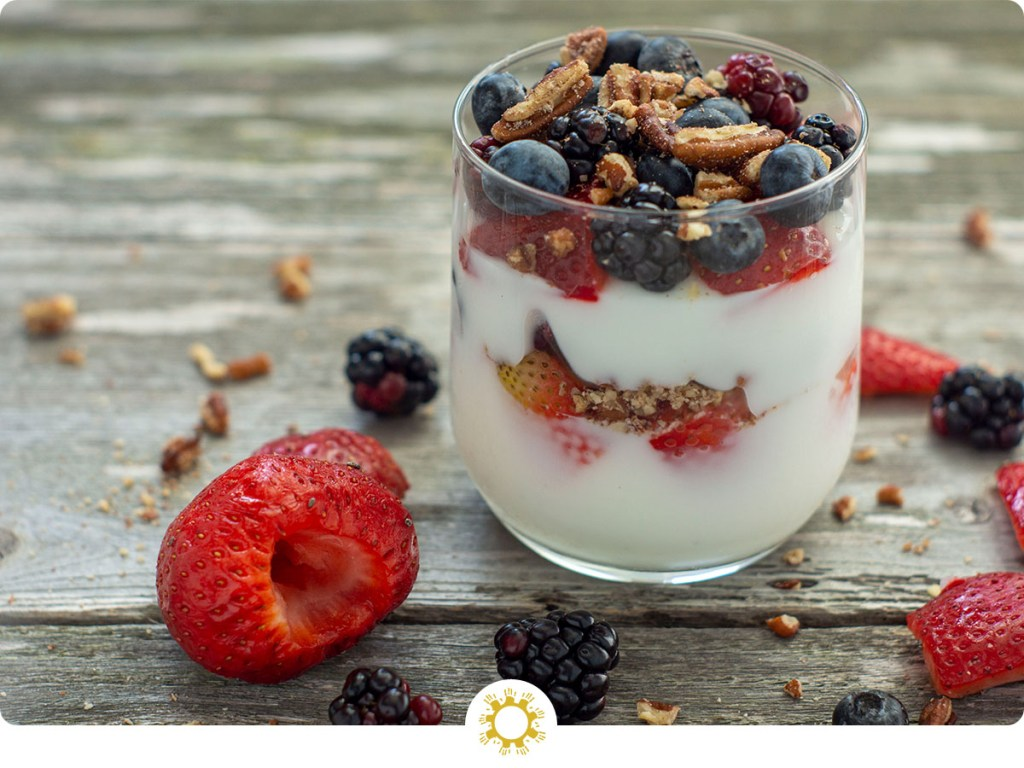 Yogurt in a glass with fruit and chopped nuts on a wooden background with ingredients around it (with logo overlay)