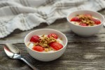 Two small bowls with yogurt and strawberries with granola on a wooden background next to a spoon